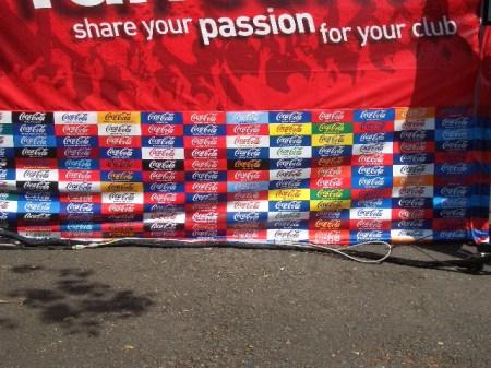 """""""Impartaseste-ti pasiunea pentru clubul tau"""". Sub umbrela forului Football League sunt 72 cluburi profesioniste, reprezentate prin culorile lor pe panoul de publicitate al sponsorului ligilor a doua, a treia si a patra, Coca Cola."""